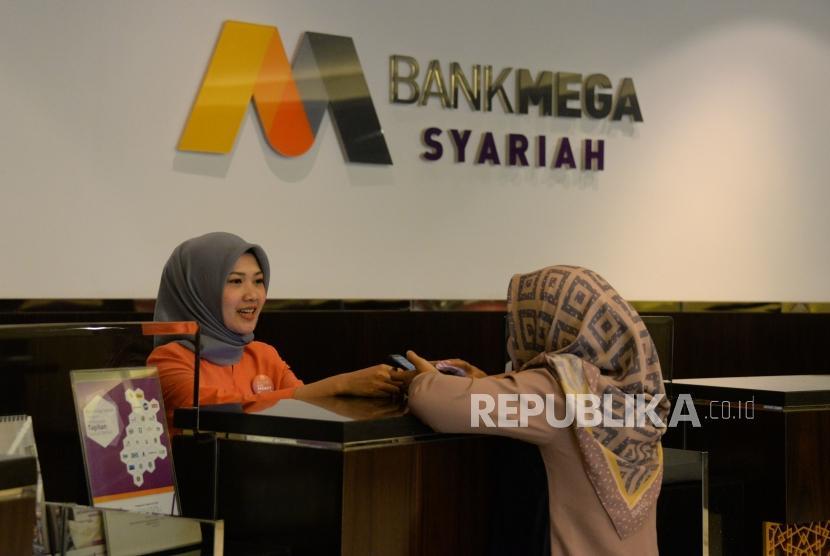 Petugas melayani nasabah di Bank Mega Syariah, Jakarta,Rabu (28/11).