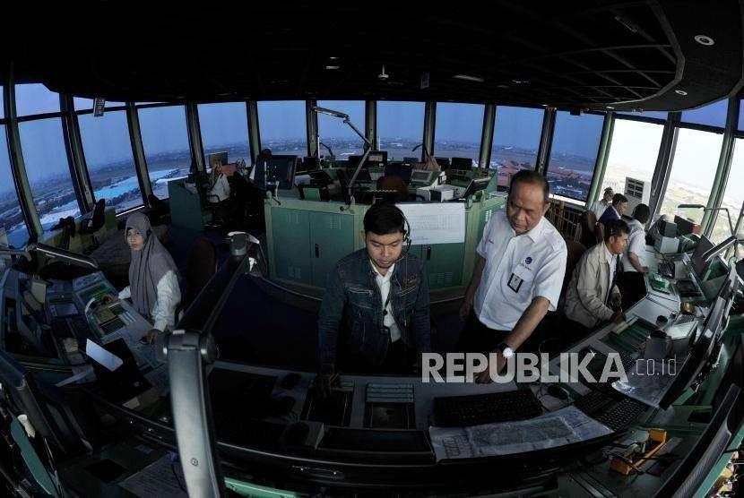 Pemandu lalu lintas udara AirNav Indonesia memantau pergerakan lalu lintas udara pesawat melalui layar radar di menara kontrol (Air Traffic Controller/ATC) Bandara Internasional Soekarno-Hatta, Tangerang, Banten, Senin (6/8).