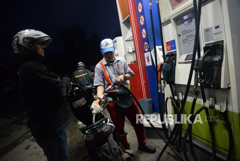 Petugas membantu konsumen mengisi Bahan Bakar Minyak (BBM) jenis pertalite pada kendaraan di SPBU Yos Sudarso, Jakarta, Ahad (25/3).