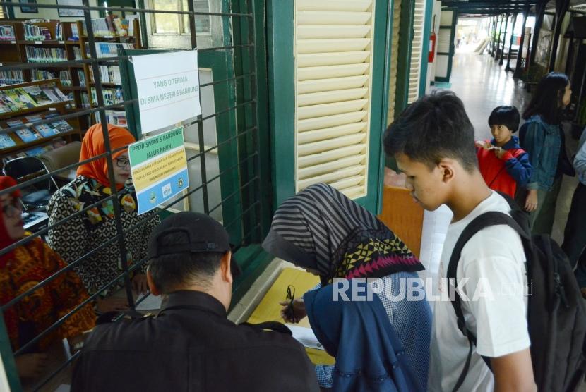 Sejumlah orang tua murid menandatangani daftar nama anaknya yang diterima di SMAN 5 Bandung, melalui jalur PPDB, di Jalan Belitung, Kota Bandung, Kamis (12/7).