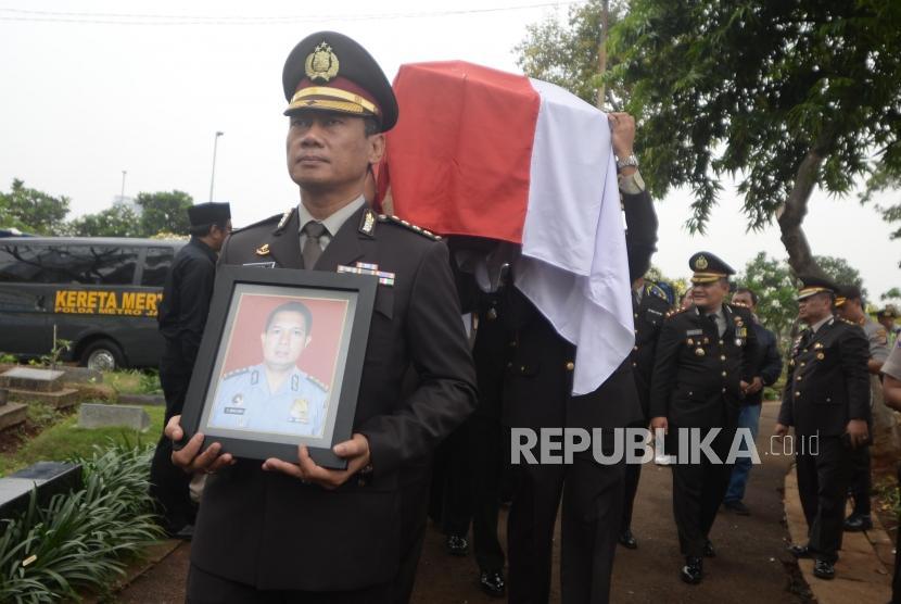 Anggota kepolisian membawa foto dan peti jenazah saat pemakaman korban jatuhnya pesawat Lion Air PK-LQP, AKBP Sekar Maulana di TPU Karet Bivak, Jakarta, Kamis (8/11).