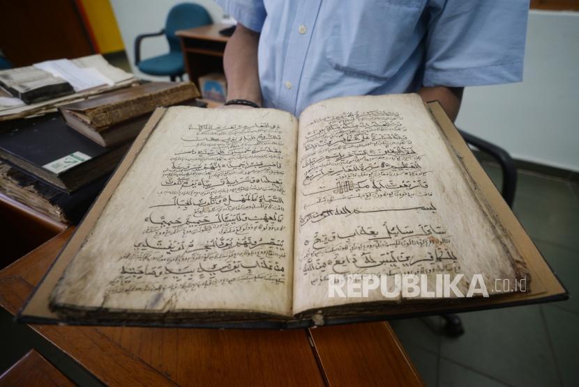Petugas Museum Bayt Alquran menunjukan mushaf Alquran berbahan daluang ( kayu pohon daluang) di Museum Bayt  Alquran, Jakarta,Rabu (5/12).