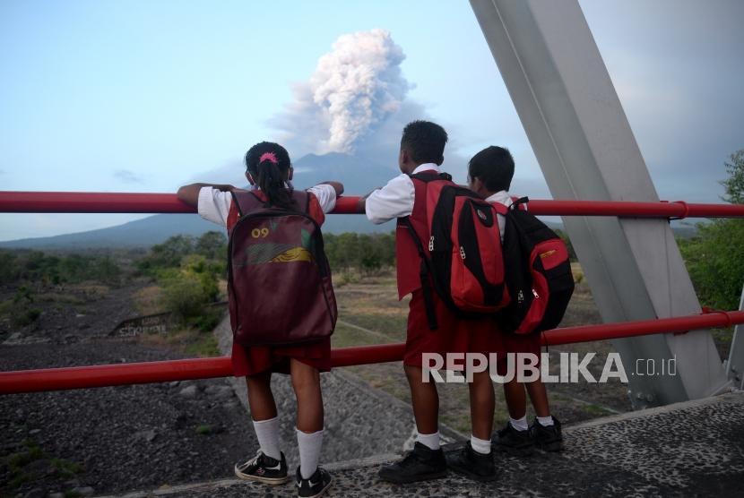 Erupsi Magmatik Masih Terjadi. Anak sekolah melihat erupsi magmatik Gunung Agung dari Kubu, Karangasem, Bali, Selasa (28/11).