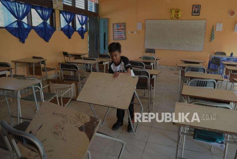 Aktivitas Pendidikan : Siswa SMP Negeri 6 mengangkat meja belajar saat melihat kondisi sekolahnya di Jalan Dewi Sartika, Palu, Sulawesi Tengah, Senin (8/10).