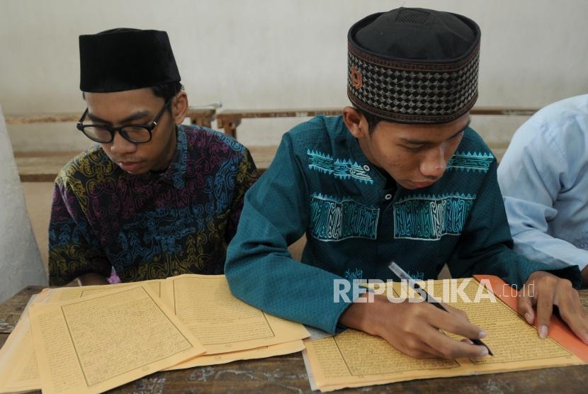 Santri belajar mengartikan Kitab Kuning saat mengaji kilatan kitab di Pondok Pesantren Almiizan, Bogor, Jawa Barat, Senin (21/5).