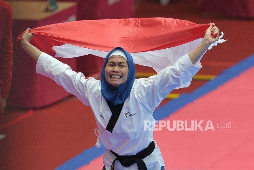 Atlet taekwondo putri Indonesia Defia Rosmaniar melakukan selebrasi seusai meraih medali emas dalam cabang taekwondo nomor poomsae Asian Games 2018 di Jakarta Convention Center, Senayan, Jakarta, Ahad (19/8).