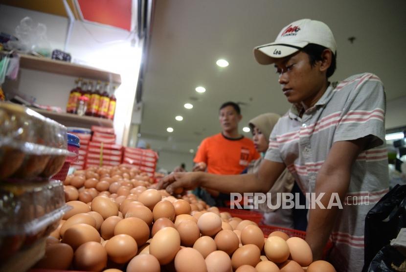 Pembeli memilih telur ayam negeri di pasar tradisional.