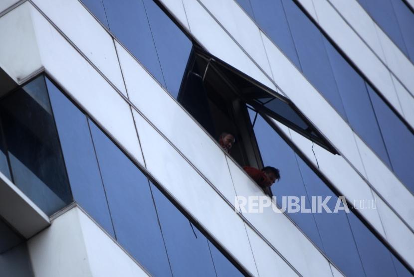 Sejumlah petugas damkar berada didalam gedung saat melakukan proses penyisiran pasca kebakaran di gedung Kementerian Perhubungan, Jakarta, Ahad (8/7).