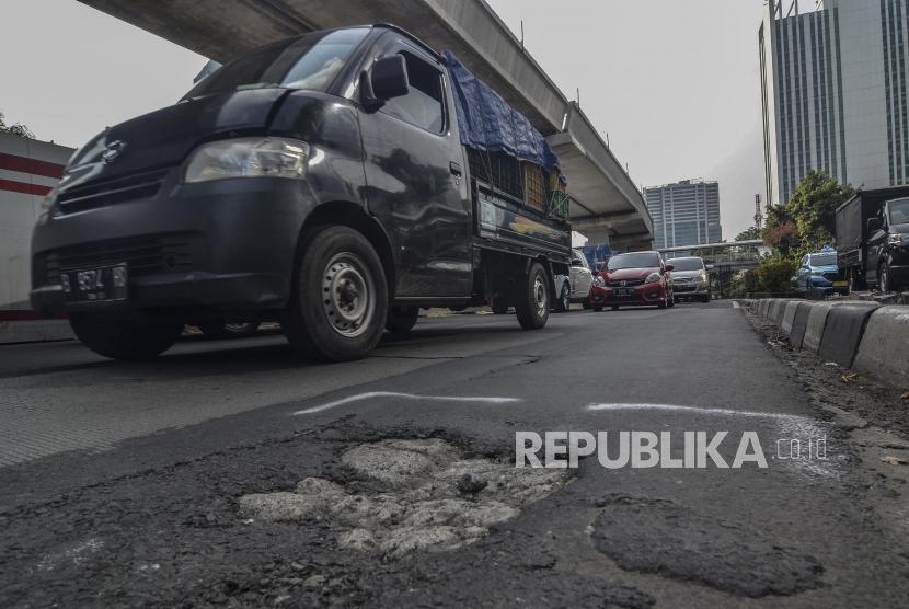 Sejumlah kendaraan melintasi jalan rusak di Jl.H.R.Rasuna Said Kuningan, Jakarta Selatan, Senin (13/5).