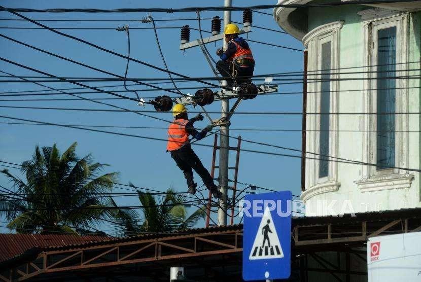 Sejumlah petugas memperbaiki jaringan PLN di Jalan Sis Al Jufri, Palu, Sulawesi Tengah, Jumat (5/10).