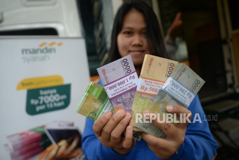 Penukaran Pecahan Rupiah. Nasabah usai menukarkan uang di mobil kas keliling Bank Syariah Mandiri di Lapangan IRTI Monas, Jakarta, Rabu (23/5).