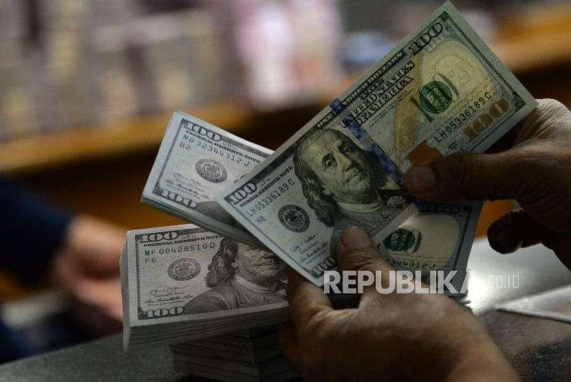 Petugas menghitung uang pecahan dolar Amerika Serikat di gerai penukaran mata uang asing di Jakarta, Selasa (2/10).