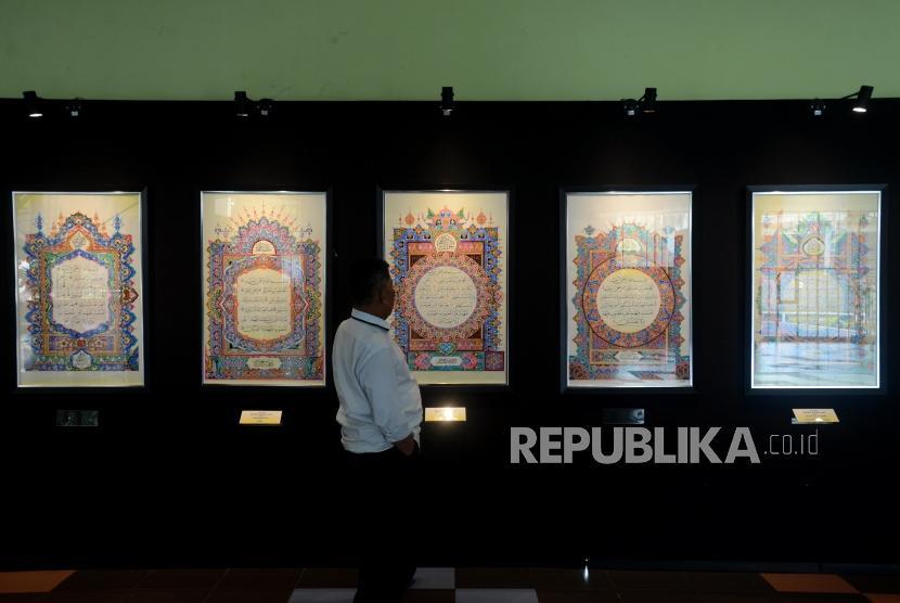 Pengujung melihat lukisan kaligrafi yang dipamerkan pada Festival Seni Kaligrafi Islam Indonesia di Gedung Bayt Al-Quran TMII, Jakarta, Senin (14/1).
