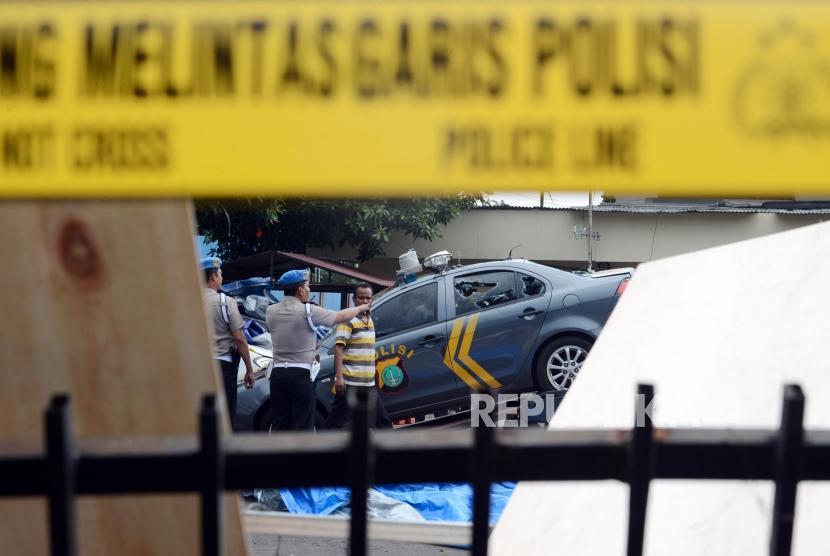 Sejumlah petugas kepolisian mengevakuasi mobil yang hancur pasca peristiwa perusakan dan pembakaran di gedung Polsek Ciracas, Jakarta, Rabu (12/12).