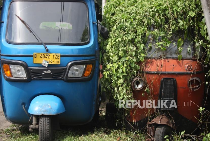 Bajaj biru terparkir disamping bangkai bajaj oranye di Kawasan Roxy, Jakarta, Ahad (4/3).