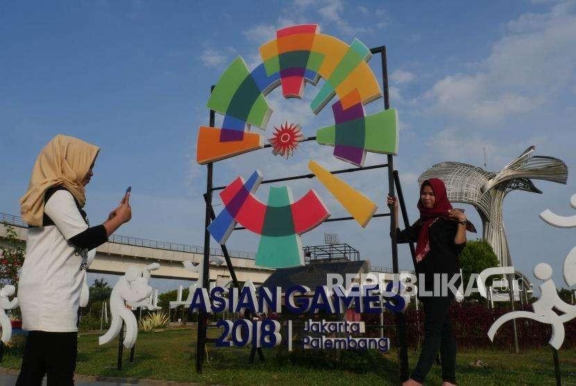 Dua  remaja saling berswa foto di depan logo Asian Games yang terletak di bundaran komplek Jakabaring Sport City, Palembang, Jumat (3/8).