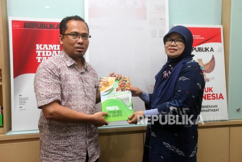 Wakil Direktur Pembina Daerah LPPOM MUI Osmena (kanan) menyerahkan buku kepada Wakil Pemimpin Redaksi Nur Hasan Murtiaji (kiri) saat kunjungan ke Kantor Harian Republika, Jakarta, Jumat (19/10).
