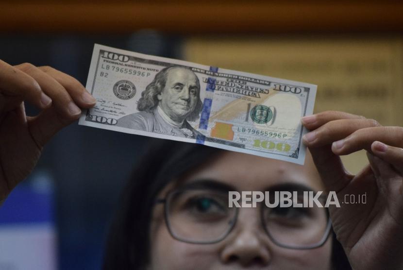 Petugas memeriksa mata uang dolar AS di salah satu tempat penukaran uang. ilustrasi