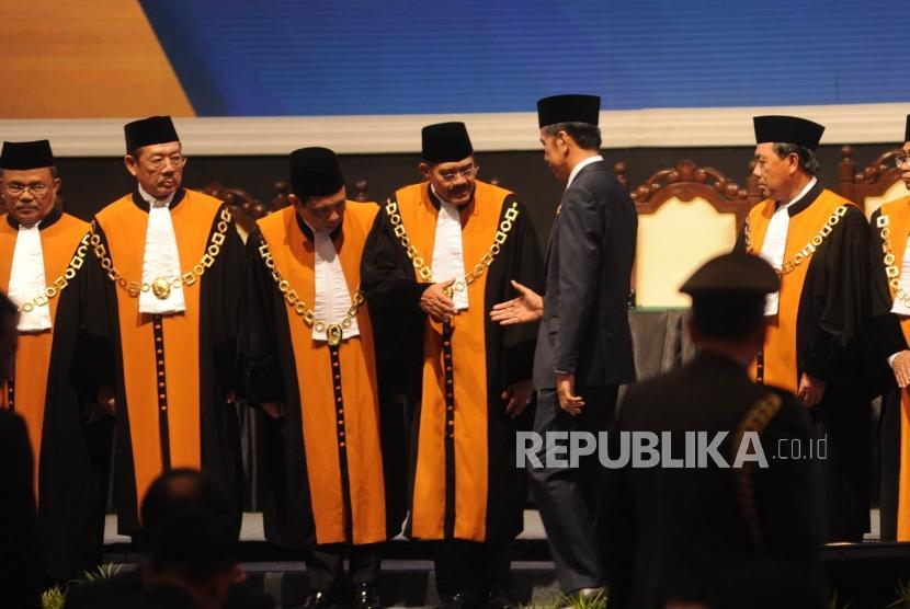 Presiden Republik Indonesia Joko Widodo bersalaman bersama Ketua Mahkamah Agung (MA) Hatta Ali usai berfoto bersama dalam acara laporan tahunan Mahkamah Agung (MA) di JCC, Jakarta, Kamis (1/3).