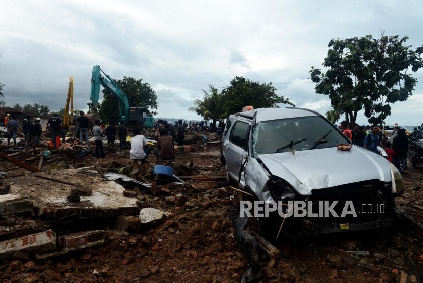 Sejumlah warga melihat alat berat melakukan evakuasi bangunan yang terdampak tsunami di Desa Way Muli, Kalianda, Lampung Selatan, Senin (24/12).