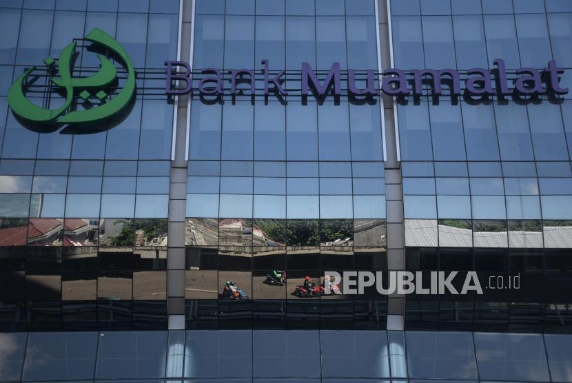 refleksi kendaraan melintas di depan kantor pusat Bank Muamalat, Jakarta, Ahad (1/4).