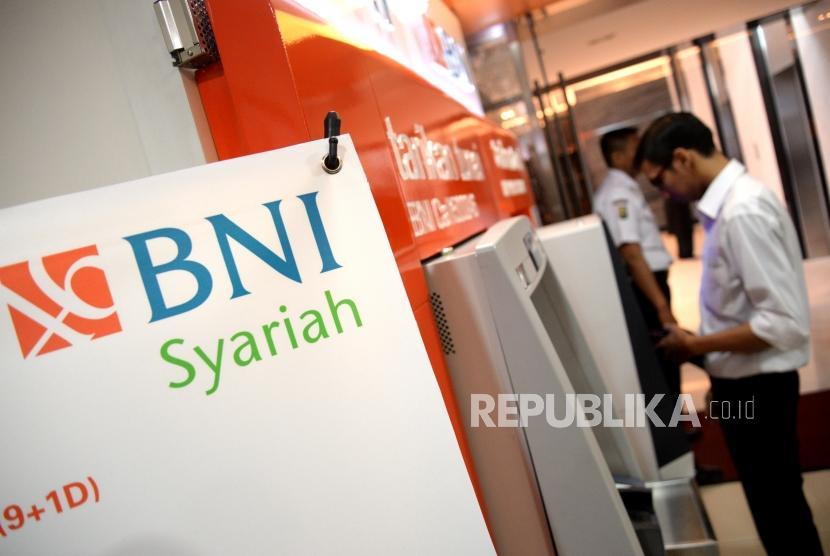 Nasabah melakukan transaksi melalui atm di kantor layanan BNI Syariah, Jakarta, Senin (11/12).