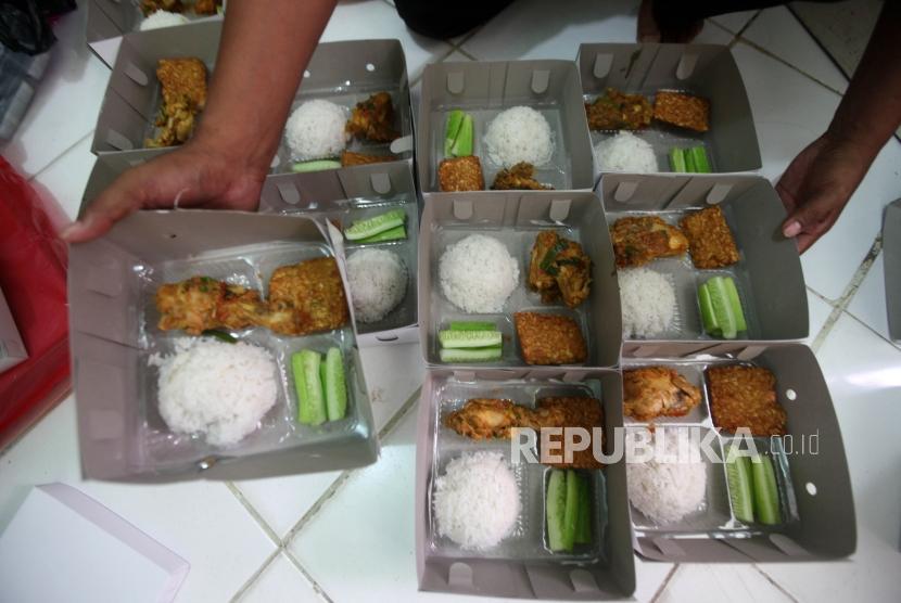 Para relawan menata nasi kotak untuk berbuka puasa bersama didapur umum di Kawasan Sawah Lio, Tambora, Jakarta, Ahad (20/5).