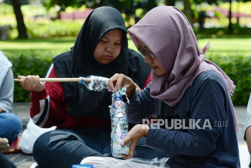 Sejumlah anggota Komunitas Jakarta Ecobrick memadatkan sampah plastik ke dalam botol di Taman Suropati, Jakarta, Ahad (16/12).