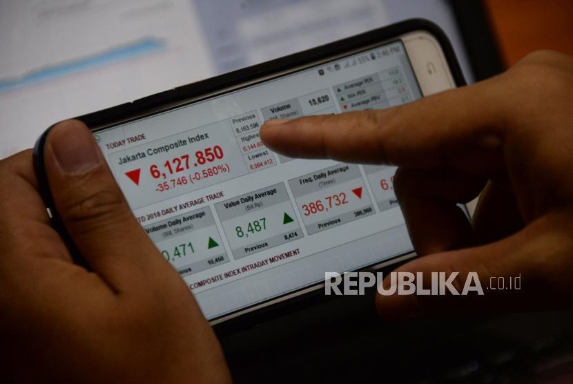 Seorang karyawan mengamati pergerakan Indeks Harga Saham Gabungan (IHSG) melalui gadget.  Ilustrasi