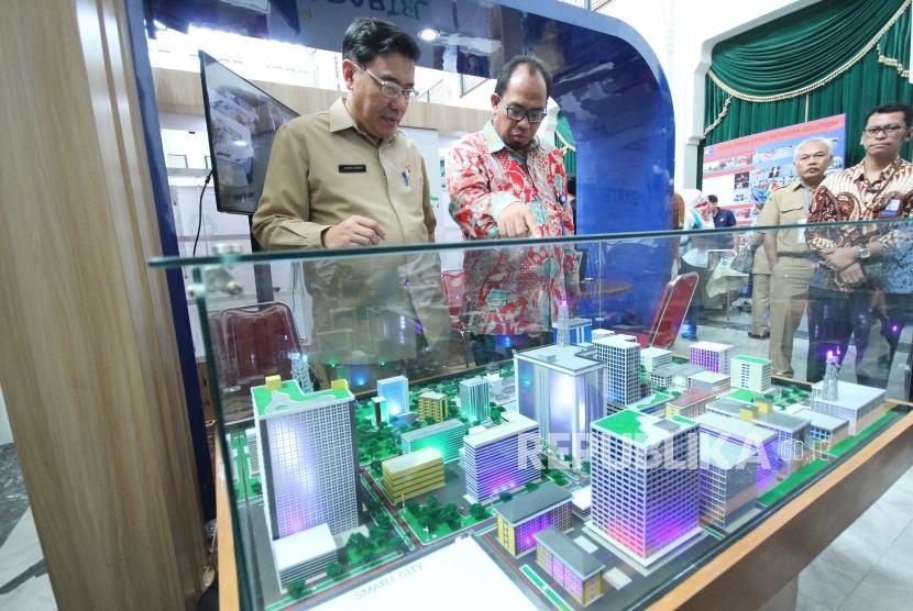Kepala Dinas Komunikasi dan Informatika Jawa Barat Hening Widiatmoko (kiri) dan Direktur Utama PT Jabar Telematika Aliyas (kanan) meninjau maket konsep Smart City saat Workshop Smart City, di Aula Timur, Gedung Sate, Kota Bandung, Senin (14/5).