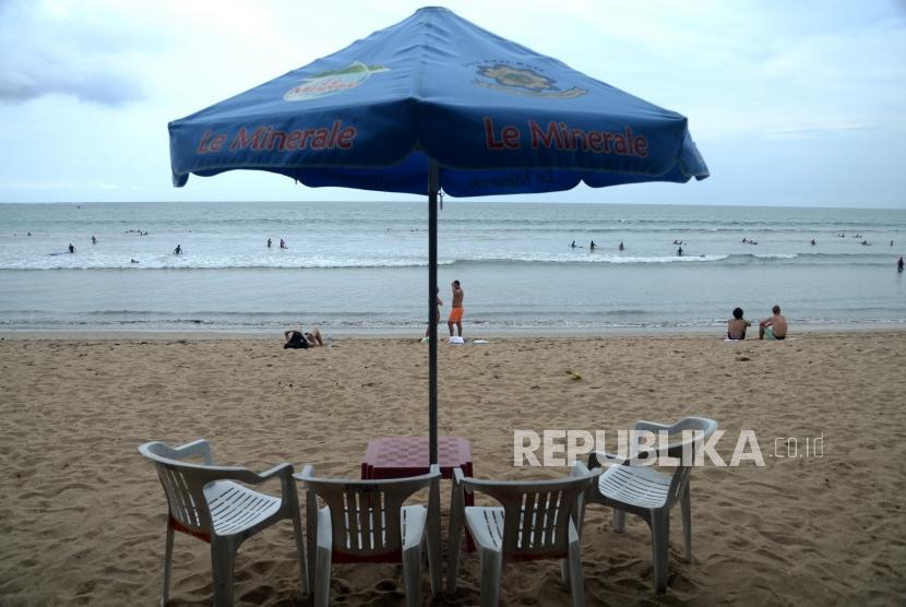 Terdampak Langsung Erupsi. Wisatawan berlibur di Pantai Kuta, Bali, Senin (27/11).