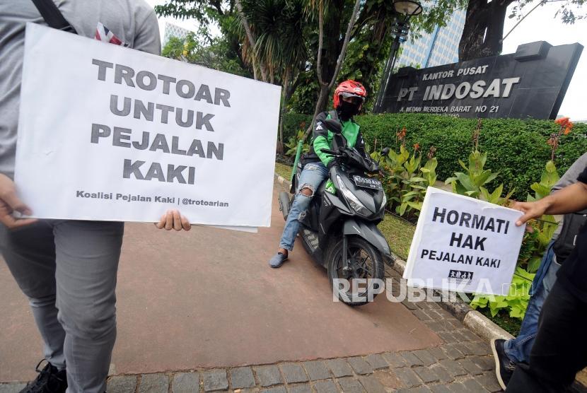 Sejumlah relawan Koalisi Pejalan Kaki melakukan aksi di trotoar Jalan MH. Thamrin, Jakarta Pusat, Jumat (12/1).