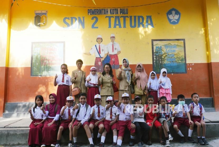Sejumlah siswa dan guru SD Negeri 2 Tatura Palu, Sulawesi Tengah berfoto bersama di halaman seklahnya, Senin (15/10).