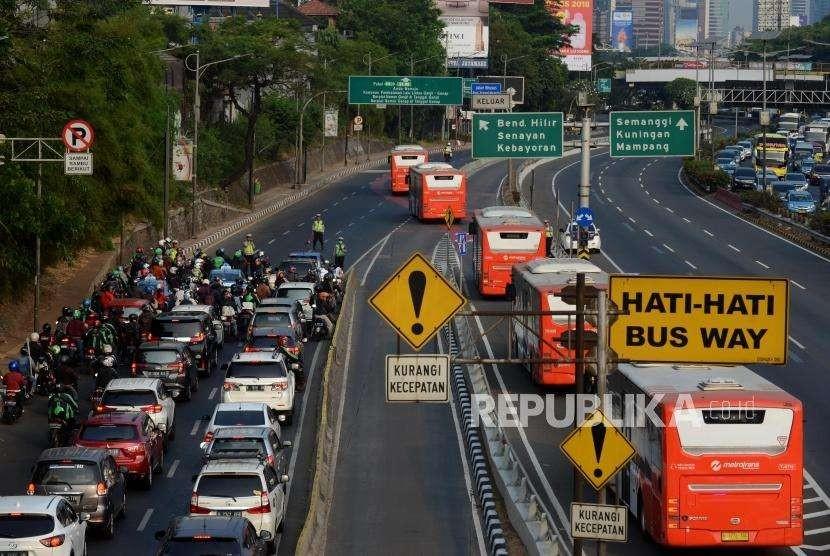 Sejumlah petugas kepolisian menjaga iring-iringan bus saat simulasi perjalanan kontingen peserta peserta Asian Games 2018 di kawasan Gatot Subroto, Jakarta, Sabtu (4/8).