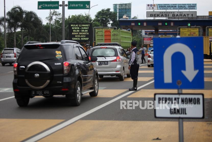 Petugas Dishub mengatur lalu lintas saat hari pertama pemberlakuan sistem ganjil genap di Gerbang Tol Bekasi Barat 1, Bekasi, Jawa Barat, Senin (12/3).