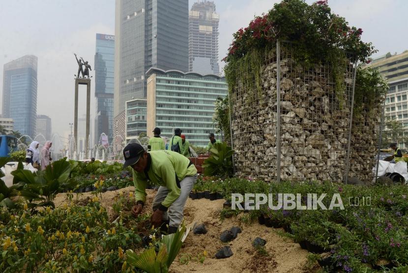 Petugas menyusun tanaman di dekat instalasi batu gabion di Bundaran HI, Jakarta, Jumat (23/8).
