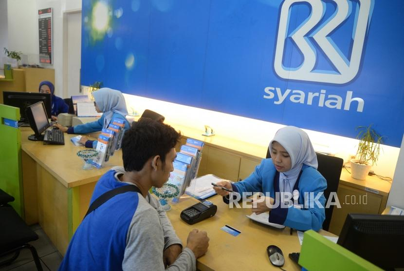 Target Perolehan Laba. Petugas melayani transaksi nasabah di kantor layanan BRI Syariah, Jakarta, Senin (2/7).