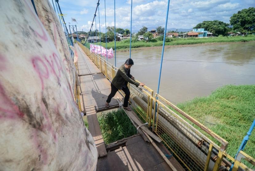Warga menyeberangi Sungai Citarum menggunakan jembatan gantung yang rusak di Rancamanyar, Kabupaten Bandung, Jawa Barat, Minggu (30/12/2018).