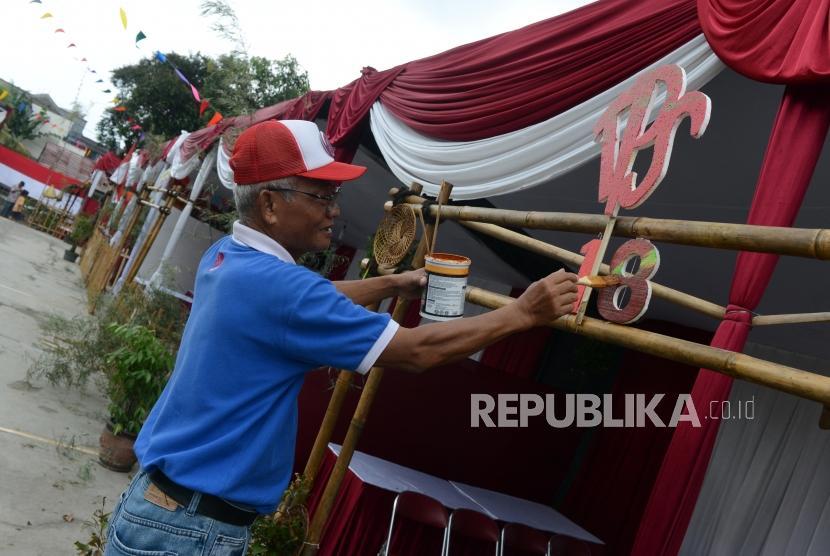 Warga saat menghias tempat pemungutan suara (TPS) di Kampoeng Pemilu Nusantara, Depok, Jawa Barat, Selasa (16/4).