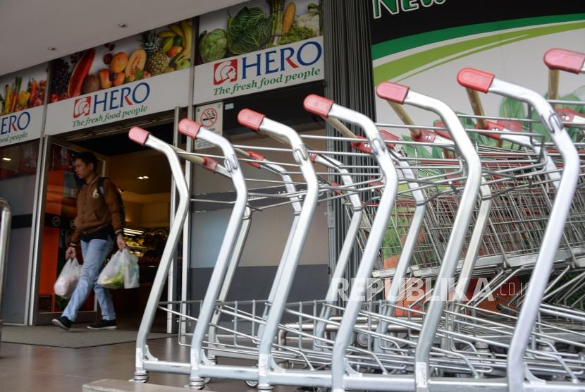 Warga keluar gerai Hero yang masih buka di kawasan Gondangdia, Jakarta, Selasa (15/1).