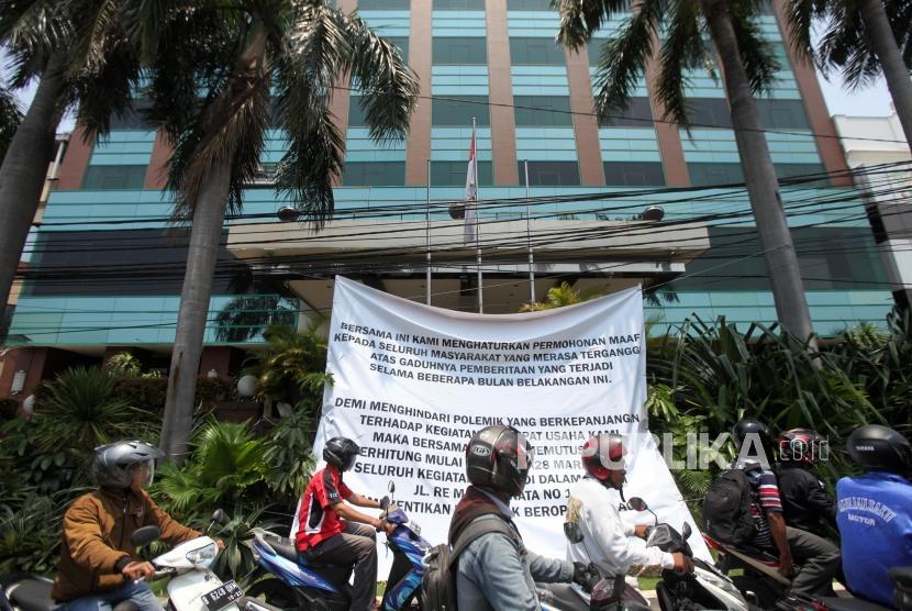 Pengendara motor melintas didepan spanduk pemberitahuan penutupan Hotel Alexis terpampang di pinggir jalan depan Alexis.Jakarta, Rabu (28/3).