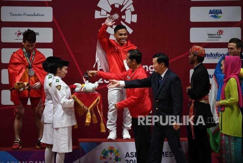 Lifter Indonesia  Eko Yuli  Irawan   (tengah)bersiap menerima medali emas yang diberikan langsung oleh Presiden Republik Indonesia Joko Widodo   usai memenang kan pertandingan  di cabang angkat besi putra nomor 62 Kg Asian Games 2018 di Hall A Kemayoran, Jakarta, selasa (21/8).