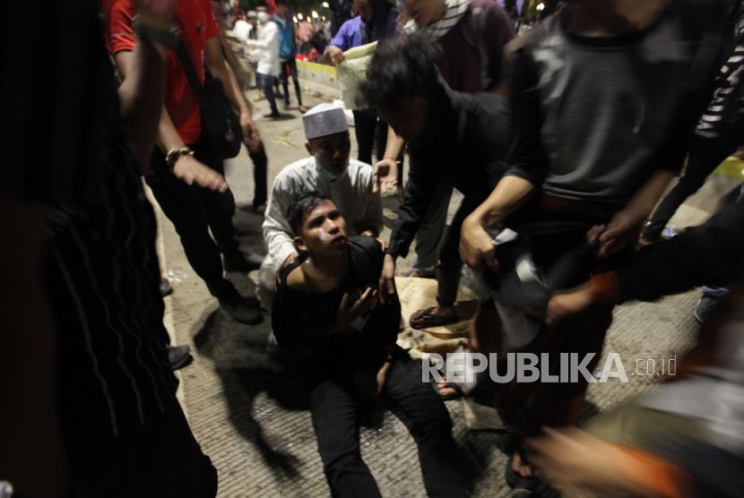 Demonstran terluka akibat gas air mata saat terlibat bentrok dengan aparat pada aksi unjuk rasa di depan gedung Bawaslu, Jakarta, Rabu (22/5).