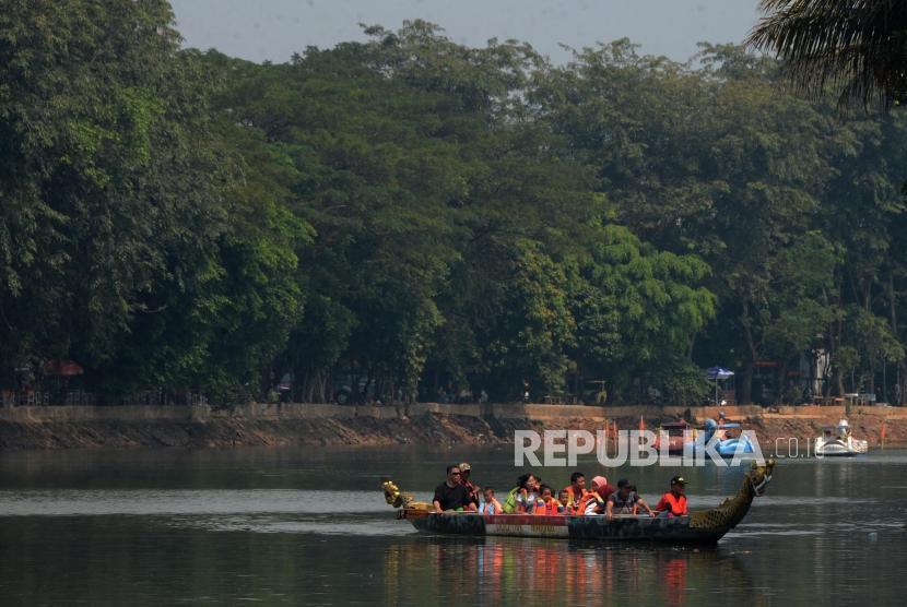 Sejumlah wisatawan saat menaiki perahu naga di Setu Babakan, Jakarta, Ahad (9/6).