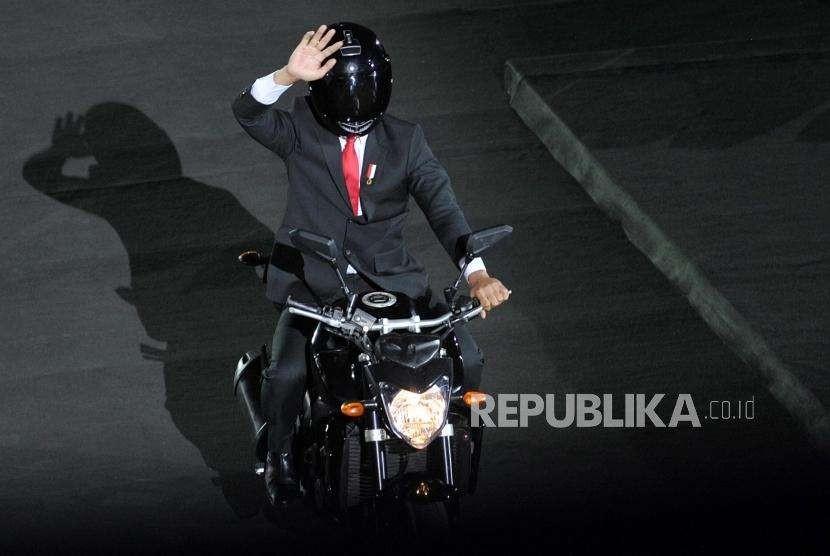 Presiden Joko Widodo menaiki motor saat pembukaan Asian Games 2018 di Stadion GBK, Senayan, Jakarta, Sabtu (18/8).
