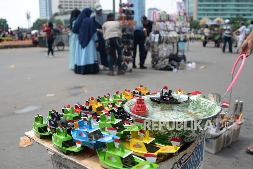 Pedagang kaki lima (PKL) berjualan di jalan saat pelaksanaan Hari Bebas Kendaraan Bermotor di kawasan Bundaran HI, Jakarta, Ahad (17/2).