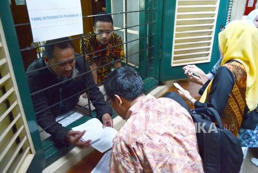Sejumlah orang tua murid menerima daftar nama anaknya yang diterima di SMA pilihan ke dua, di SMAN 5 Bandung, melalui jalur PPDB, di Jalan Belitung, Kota Bandung, Kamis (12/7).