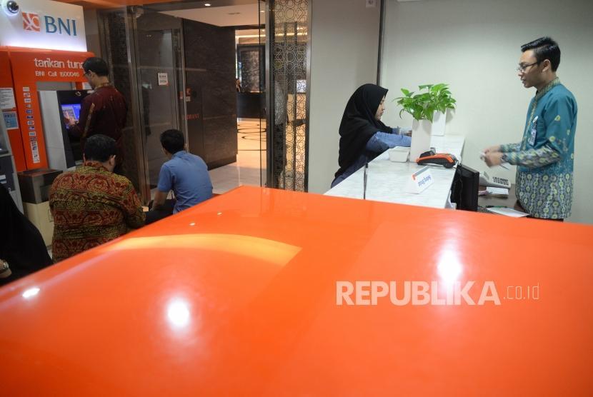 Kinerja Kuartal Pertama BNI Syariah. Petugas melayani transaksi nasabah di kantor layanan BNI Syariah, Jakarta, Rabu (25/4).