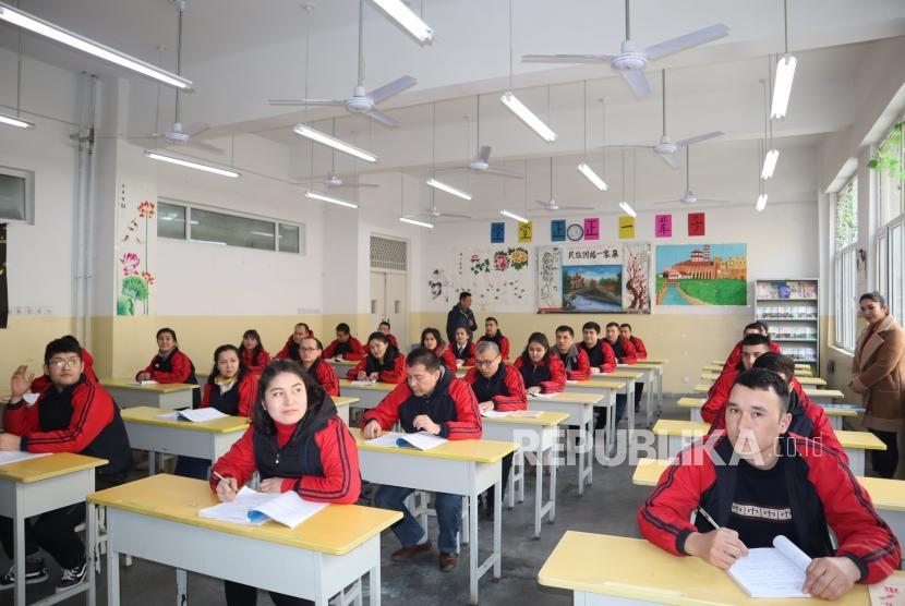 Para peserta didik kamp pendidikan vokasi etnis Uighur di Kota Kashgar, Daerah Otonomi Xinjiang, Cina, mengikuti kelas Bahasa Mandarin, Jumat (3/1/2019).