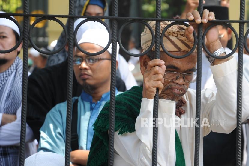 Massa   HTI saat menunggu hasil sidang pembacaan putusan gugatan Hizbut Tahrir Indonesia (HTI) di Pengadilan Tata Usaha Negara (PTUN), Jakarta, Senin (7/5).
